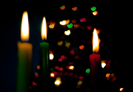 booked: three candles on the black background with hearts Stock Photo