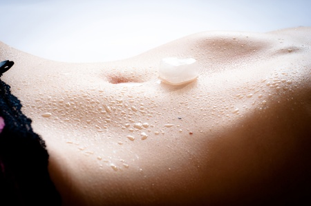 thin ice: Wet female flat tummy with a slice of ice in the form of heart