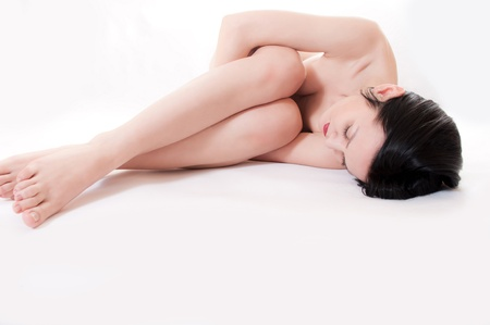 The naked young beautiful girl lies on a white background, having clasped itself hands Stock Photo - 12683645
