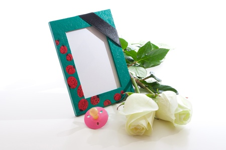 the nursery a photo frame with a mourning black tape, white roses and a children Stock Photo - 12932552