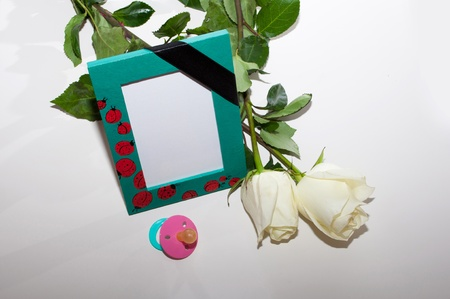the nursery a photo frame with a mourning black tape, white roses and a children Stock Photo - 12932553