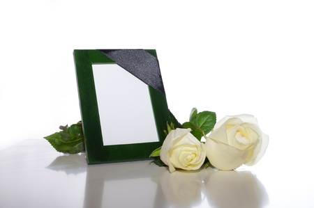 funeral background: green photo frame with a mourning black tape and white roses on a light background