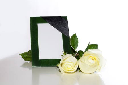 green photo frame with a mourning black tape and white roses on a light background