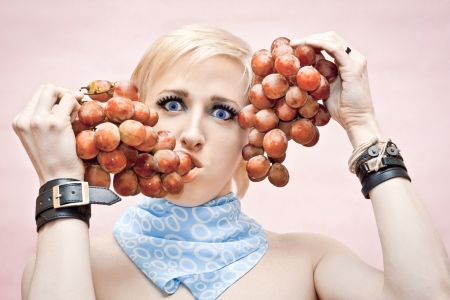sensually: the young guy the gay sensually eats grapes which holds near the person on a pink background