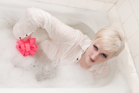 extraordinary: the young extraordinary man in a white shirt and with a red bow on a hand in a bath with foam Stock Photo