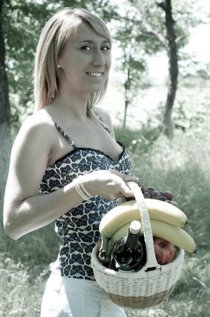 La hermosa joven al aire libre entre árboles verdes, con una cesta de frutas en las manos Foto de archivo - 14185766