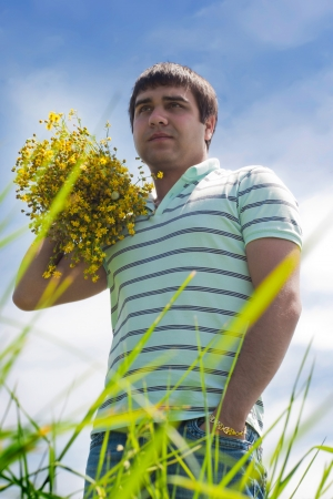 armful: the young man outdoors with an armful of wild yellow flowers
