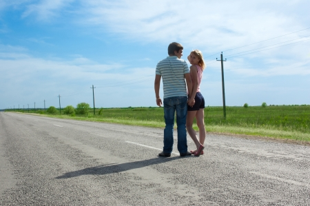 the carriageway: the young couple costs on a carriageway holding hands, spring