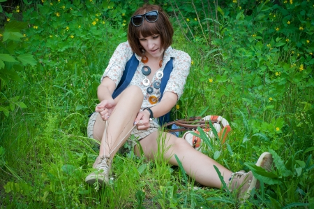 fastens: the young stylish girl sits on a spring green grass and fastens laces of the sneakers Stock Photo