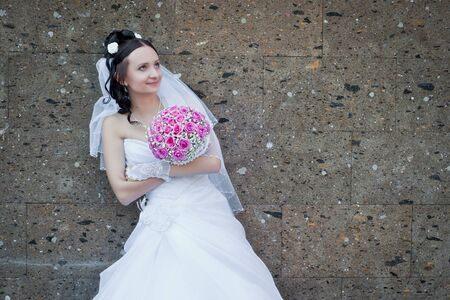 the beautiful young bride stands near a brown stone wall with a pink bouquet in hands photo