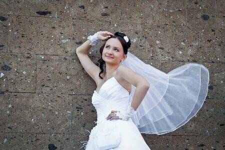 the beautiful young bride stands near a stone wall with a veil developing from a wind photo