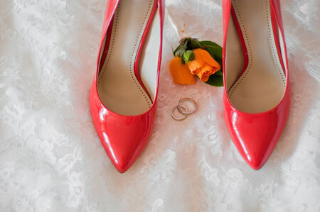 buttonhole: red shoes of the bride, wedding rings and buttonhole on a wedding dress
