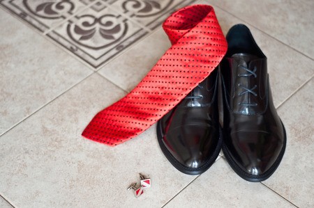 cuff links: black shoes of the groom, red tie and cuff links on a floor