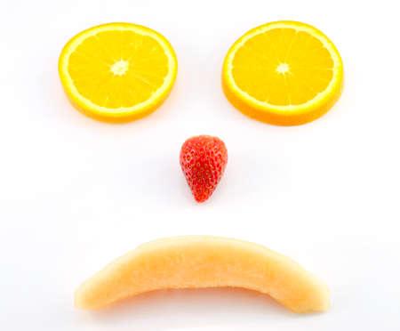 Sad face by mix fruits,orange strawberry,melon photo