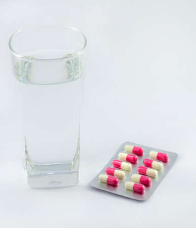 depressant: Capsules and glass of water on white background