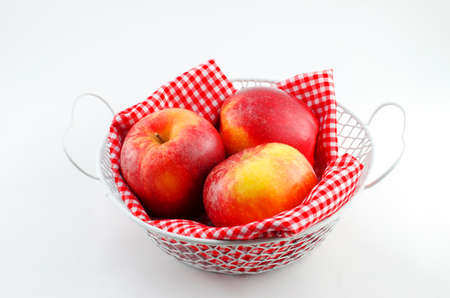 dring: Apples with red napkin in a white basket on white background