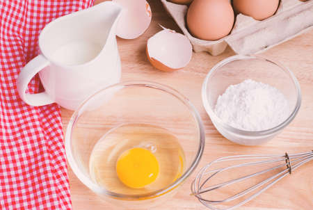 eggbeater: Cookies ingredients. Bowl flour eggs jar of milk eggbeater eggshells and red napkin Stock Photo