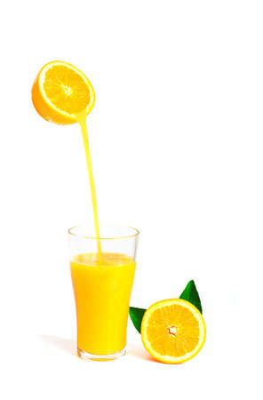 work path: orange juice pouring into glass with orange slice and leaf isolate on white with work path Stock Photo