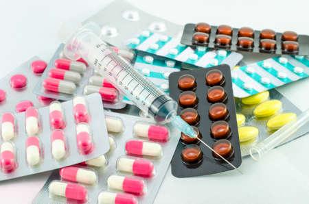 syring: Medicines pills and syringe on white background