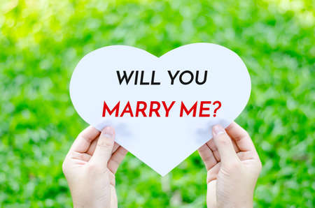 will you marry me: Hand holding white heart paper with will you marry me text on blur green grass background