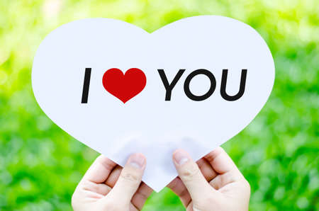 Hand holding white heart paper with I love you text on blur green grass background photo