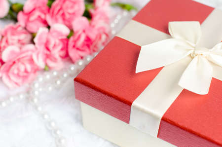 white fur: Close up of gift box with pearl necklace and pink carnation flower on white fur background