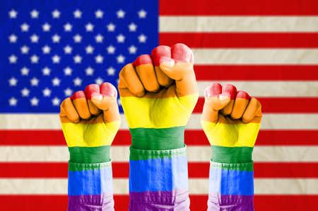 amor gay: Mano Pu�o con la bandera del arco iris con dibujos en la bandera de los estados unidos de am�rica fondo Homosexual concepto gay y el amor Corte Suprema de Estados Unidos rige el matrimonio gay es legal en todo el pa�s Foto de archivo