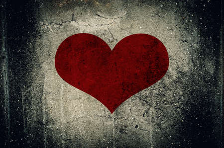 Red heart painted on grunge cement wall background - love concept Stock Photo