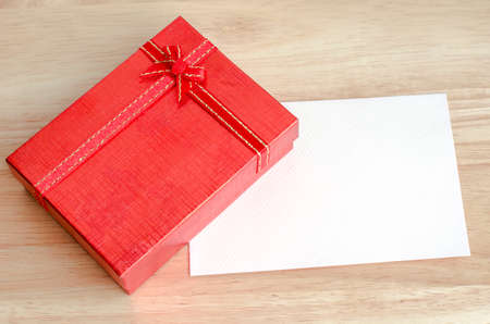 Red gift box with ribbon and blank white card on wooden table Stock Photo