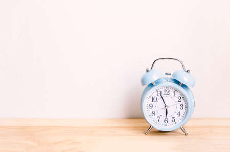 Light blue alarm clock on wooden table and white wall background with sofe vintage color