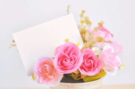 rose coloured: Pastel Coloured Artificial Pink Rose Wedding Bridal Bouquet in flower pot and white paper card with soft vintage tone Stock Photo