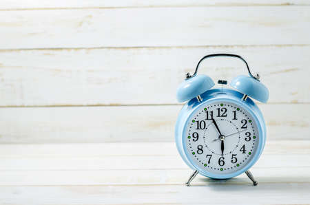 time table: Close up of Blue Vintage Alram Clock on white wooden table with place for text