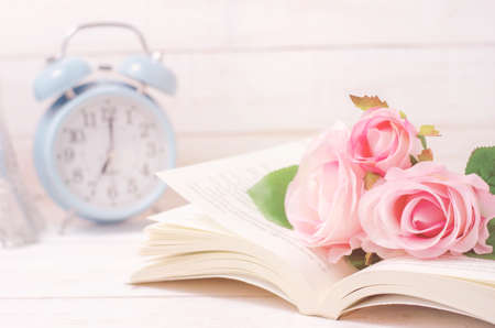 Pastel artificial rose and open book on white wooden table with soft vintage tone Archivio Fotografico