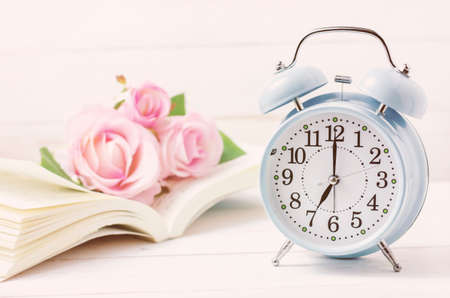 Blue retro alarm clock with book and pink pastel roses on white wooden table - Soft vintage color