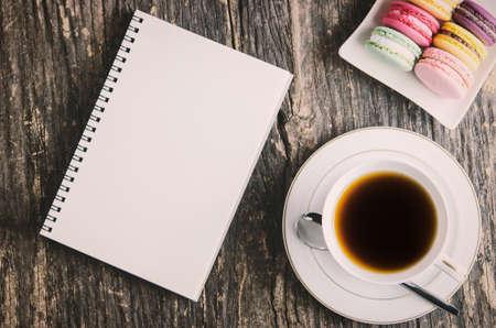 White Notebook auf Holztisch mit Tasse schwarzen Tee und bunten Makronen in weißen Teller - Weinlese und Vignette Farbe