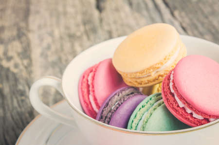 Colorful and pastel Macaroons in white coffee cup on old wooden table with vintage and vignette tone