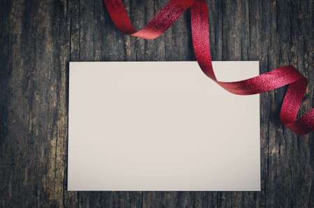 old backgrounds: Blank white greeting card and red ribbon on old wooden background with vintage and vignette tone