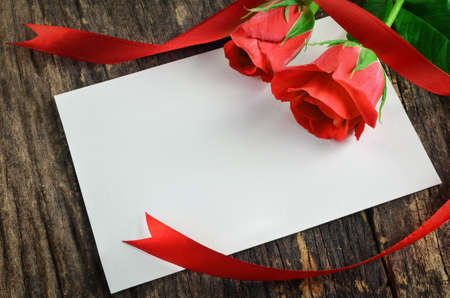 Blank white greeting paper card with red roses and ribbon on old wooden table - Love Concept