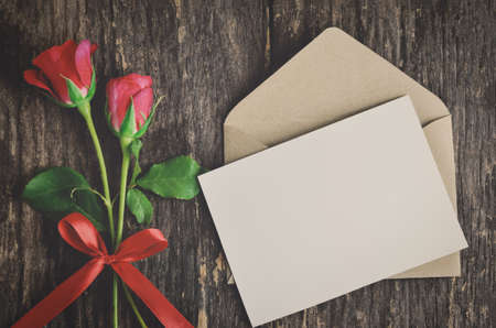 Blank white greeting card with brown envelope and red rose flowers with ribbon bow on wooden table with vintage and vignette tone - Valentine and love concept