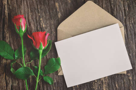 Blank white greeting card with brown envelope and red rose flowers on wooden table with vintage and vignette tone - Valentine and love concept