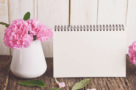 Blank Desk calendar with pink carnation flower in white vase on wooden table with vintage and vignette tone