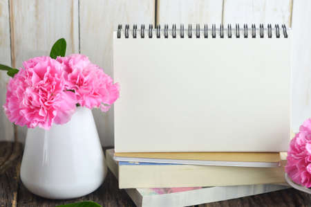 Blank Desk calendar on pile of books with pink carnation flower in white vase on wooden table