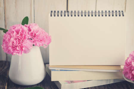 Blank Desk calendar on pile of books with pink carnation flower in white vase on wooden table with vintage and vignette tone