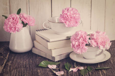 Pink pastel carnation flowers in white tea cup and vase on pile of books on wooden table with vintage tone 写真素材