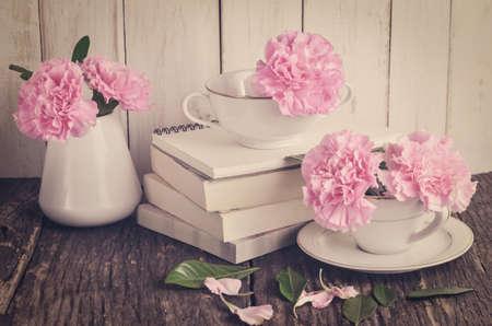 colores pastel: flores de clavel rosa en colores pastel en la taza de té blanco y el florero en la pila de libros sobre la mesa de madera con tono de época