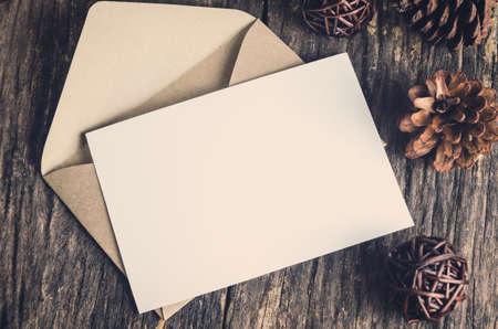 Tarjeta de papel blanco en blanco con envoltura marrón y conos de pino en la mesa de madera vieja con tono vintage y viñeta