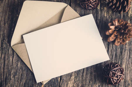 letter envelopes: Tarjeta en blanco de papel blanco con envuelve marr�n conos de pino y en tabla de madera con tono de �poca y la vi�eta