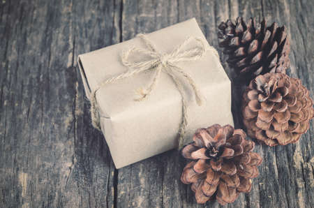 Handmade gift box with brown rope bow and pine cone on wooden table. Christmas background with vintage and vignette tone 写真素材