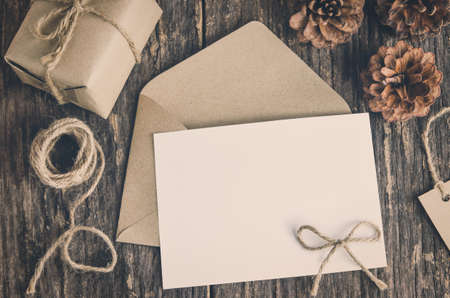 Blank white paper card with brown envelop and handmade gift box on old wooden table with vintage and vignette tone
