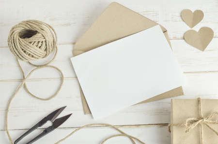 Carte de voeux vierge blanche avec enveloppe brune et une boîte cadeau à la main sur la vieille table en bois avec ton cru